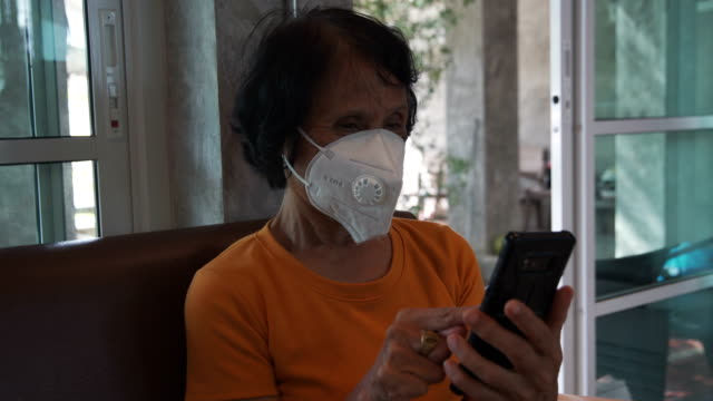 vidéos et rushes de femmes asiatiques aînées jouant le téléphone intelligent - masque de chirurgien