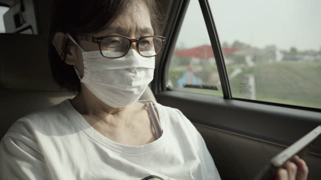 senior asian women wearing protective masks in the car. - passenger stock videos & royalty-free footage
