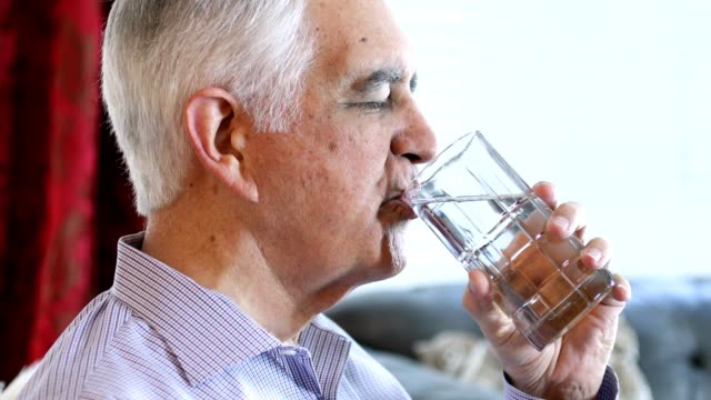 Senior at Home drinking water