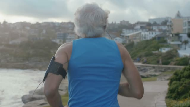 Senior athlete running at Bondai Beach (slow motion)