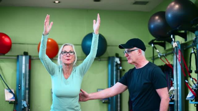 シニアアスレチックマン、パーソナルトレーナーは、ジムでの体操ボールとフィットネストレーニング中に先輩の女性にバランスの練習を支援します。 - フィットネスボール点の映像素材/bロール