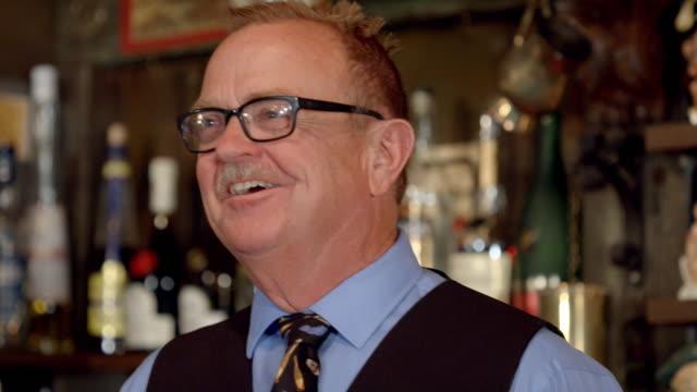 tu cu senior bartender face smiling at customers and greeting customers - hemd und krawatte stock-videos und b-roll-filmmaterial
