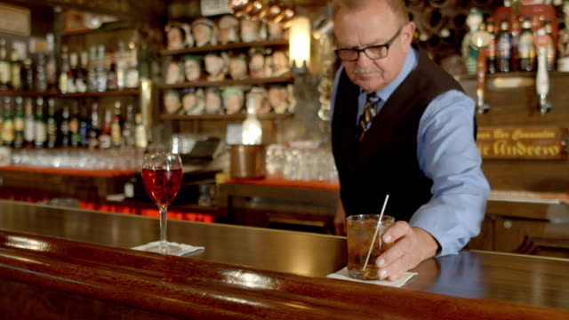 MS Senior bartender puts whiskey on-the-rocks cocktail next to glass of rose wine