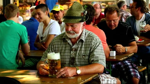 Senior Bavarian Man drinking beer in a crowded Bavarian Beergarden the Viktualienmarkt in Munich