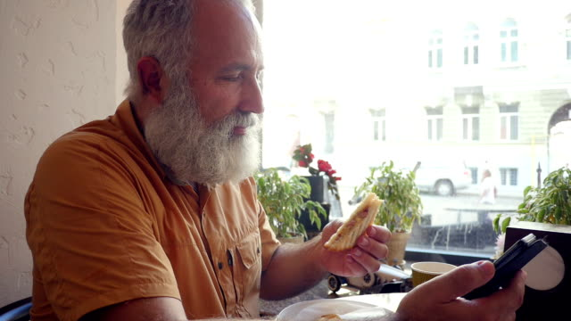 Senior bearded  Caucasian man in casual outfit drinking coffee and eating sandwich in a cafe