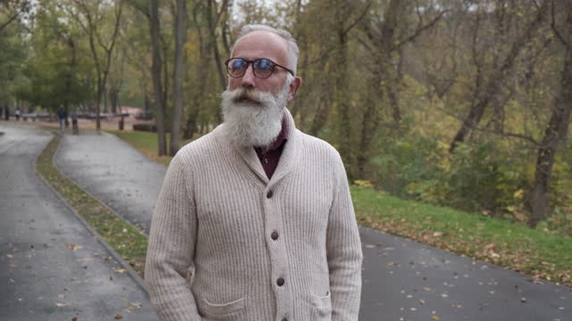 senior bearded man walking in the park. one person - grey hair stock videos & royalty-free footage