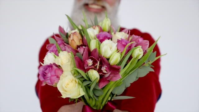 Senior bearded man with flowers on a white background. 4K
