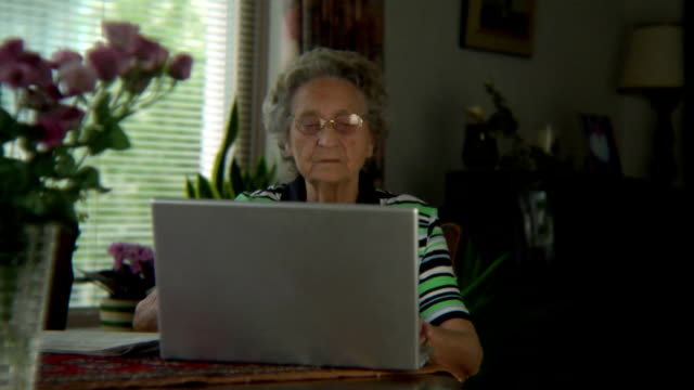 vídeos de stock e filmes b-roll de senior atrás de computador portátil - idoso na internet