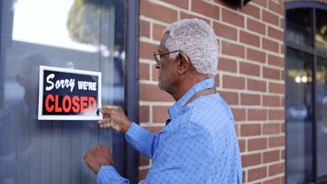senior black business owner with open sign - street name sign stock videos & royalty-free footage
