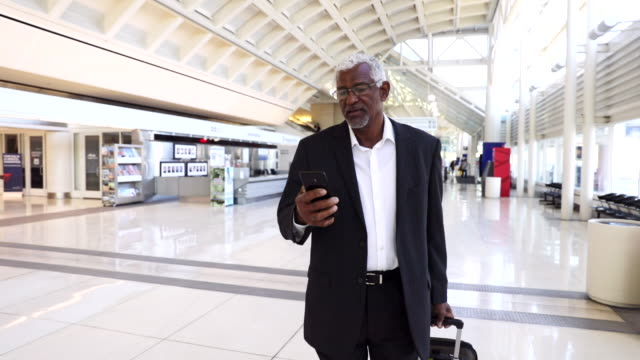senior black businessman on phone at the airport - 50 54 years stock videos & royalty-free footage