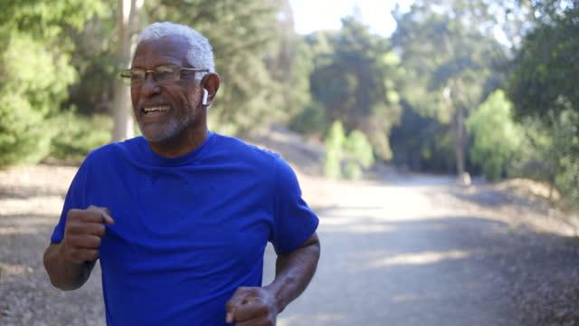 senior black man jogging outdoors - slow-motion stock videos & royalty-free footage