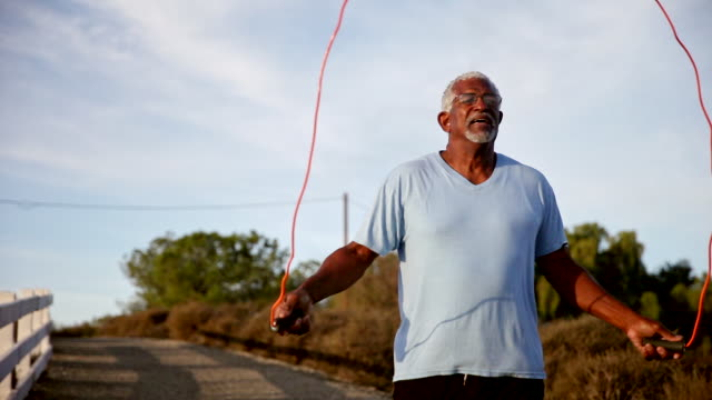 vídeos de stock e filmes b-roll de senior black man jumping rope outdoors - corda de saltar