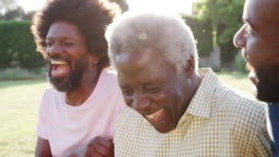 Senior black man laughing with his two adult sons, close up