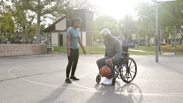 senior black man playing basketball with daughter in wheelchair - basketball sport stock videos & royalty-free footage