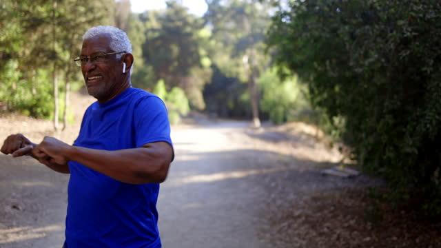 vidéos et rushes de senior black man stretching pour l'entraînement - lunettes de vue