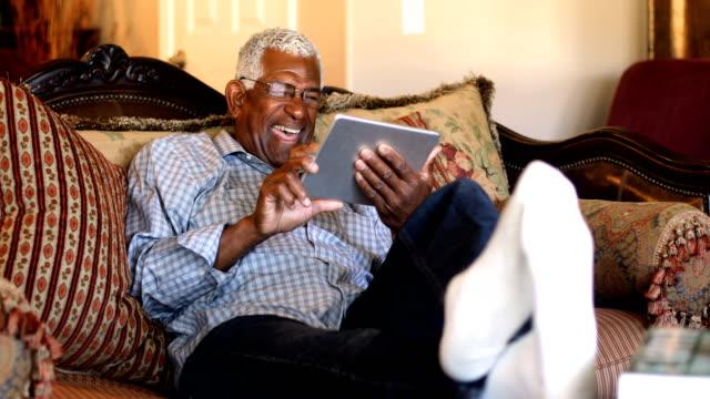 vídeos de stock, filmes e b-roll de homem negro sênior usando tablet em casa - assistir tv