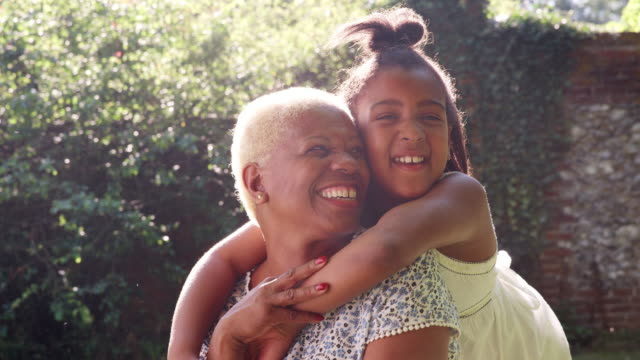 Senior black woman and granddaughter sit embracing outside