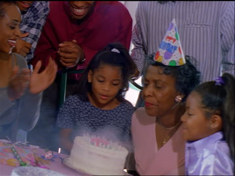 CANTED PAN senior Black woman blowing out birthday candles with help from two girls / they kiss her