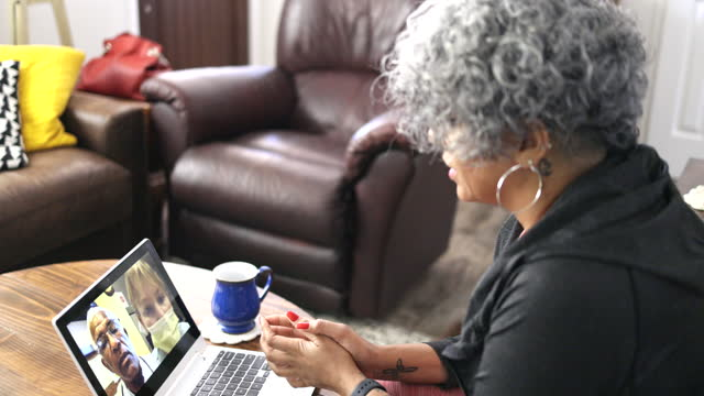 senior black woman on video call with doctors - over the shoulder stock videos & royalty-free footage