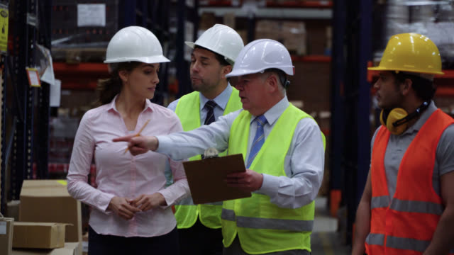 senior boss discussing with his business team and warehouse supervisor while checking his clipboard and pointing at different shelves - world trade organisation stock videos & royalty-free footage