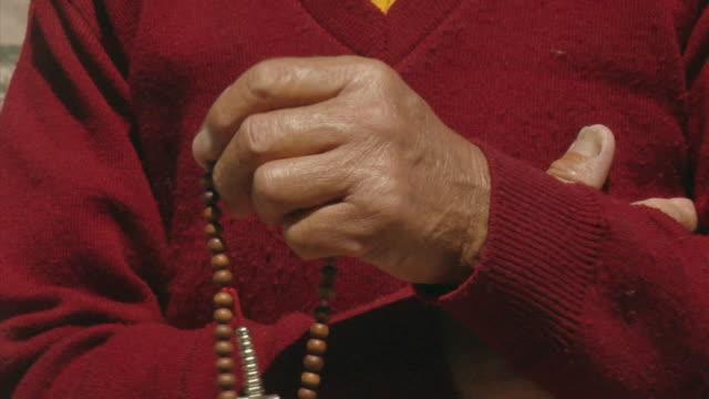vídeos de stock, filmes e b-roll de cu, senior buddhist monk with prayer beads, close-up of hands, leh, ladakh, jammu and kashmir, india - buddhism