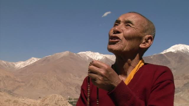 cu, senior buddhist monk with prayer beads in mountain landscape, leh, ladakh, jammu and kashmir, india - monk stock videos & royalty-free footage