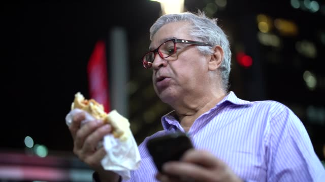 senior business man eating hot dog on the street - unhealthy eating stock videos & royalty-free footage