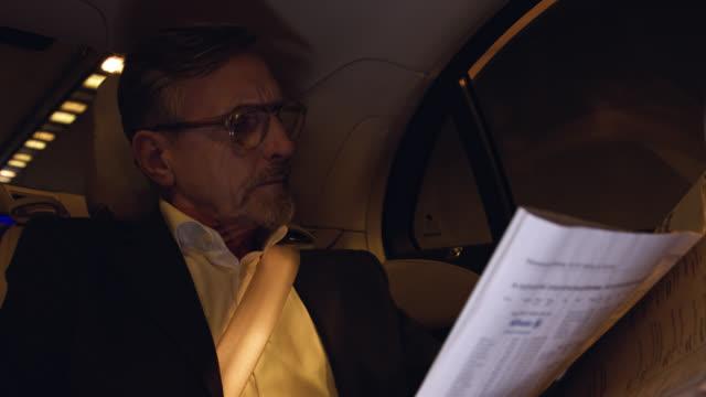 senior business man gets chauffeured in luxury limousine while reading newspaper - beifahrersitz oder rücksitz stock-videos und b-roll-filmmaterial