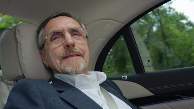 vídeos y material grabado en eventos de stock de senior business man in his 60s gets chauffeured home in luxury limousine electric car - coche eléctrico coche alternativo