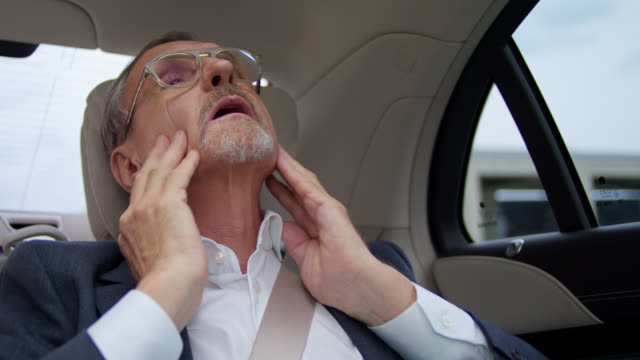 senior business man in his 60s gets chauffeured in luxury limousine while checking his styling in a mirror - beifahrersitz oder rücksitz stock-videos und b-roll-filmmaterial
