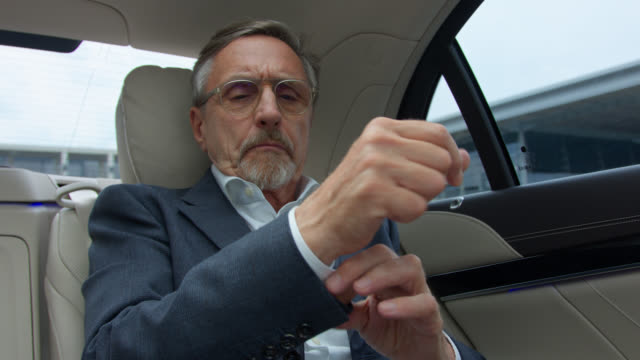 senior business man in his 60s gets chauffeured in luxury limousine he buttons his shirt and starts using digital tablet - beifahrersitz oder rücksitz stock-videos und b-roll-filmmaterial