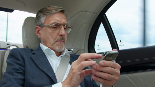 senior business man in his 60s gets chauffeured in luxury limousine while using his smart phone - part of a series stock-videos und b-roll-filmmaterial