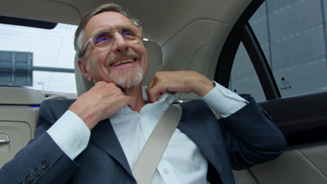 senior business man in his 60s gets chauffeured in luxury limousine, he is checking his styling in mirror - blickwinkel der aufnahme stock-videos und b-roll-filmmaterial