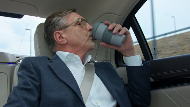 senior business man in his 60s gets chauffeured in luxury limousine and drinks coffee from reusable coffee cup - prosperity stock videos & royalty-free footage