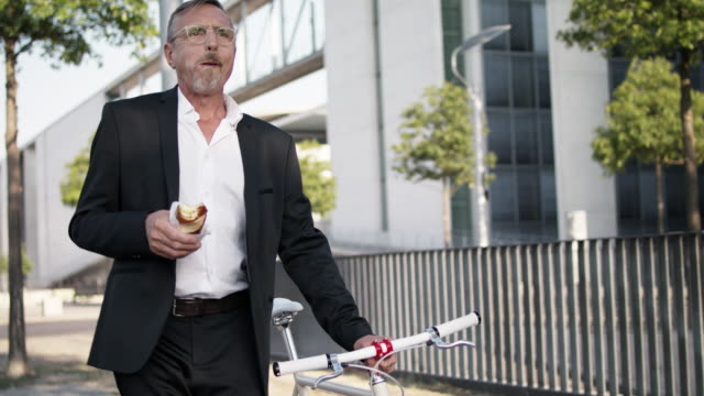 senior business man in his early 60s with short greying hair and grey beard enjoys urban lifestyle in summer, he wears a black garment while having a quick lunch on the go and pushing his trendy city bike. - schnellkost stock-videos und b-roll-filmmaterial