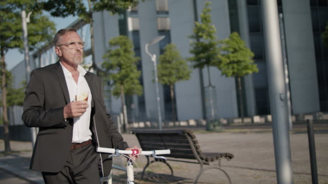 senior business man in his early 60s with short greying hair and grey beard enjoys urban lifestyle in summer, he wears a black garment while having a quick lunch on the go and pushing his trendy single speed city bike. - zerbrechen stock-videos und b-roll-filmmaterial