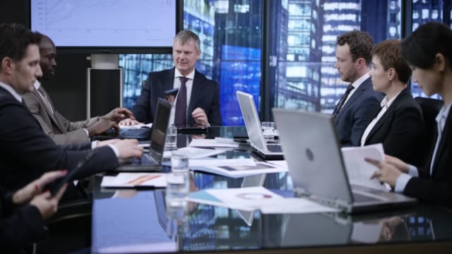 senior business man leading the meeting in a glass walled conference room in the evening - medium group of people stock videos & royalty-free footage