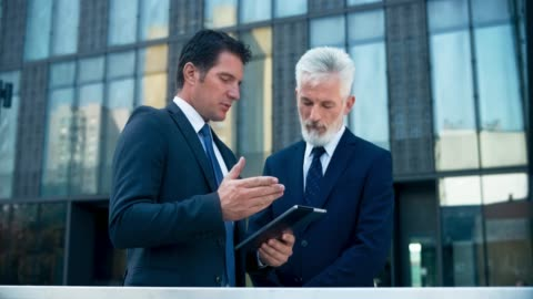 ds senior business man listening to his younger colleague asking for advice in front of the business building - business stock videos & royalty-free footage