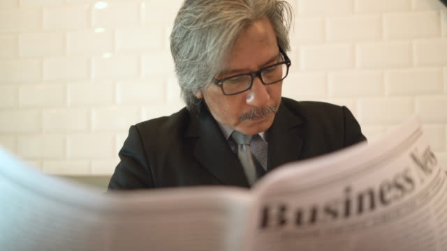 senior business man reading a newspaper in coffee cafe shop. - businesswear stock videos & royalty-free footage