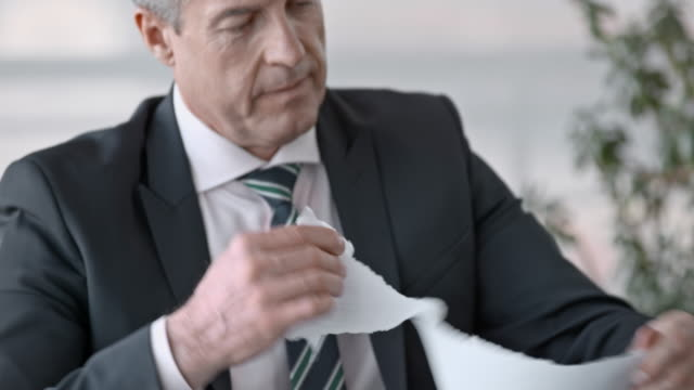 Senior business man tearing up a document in his office