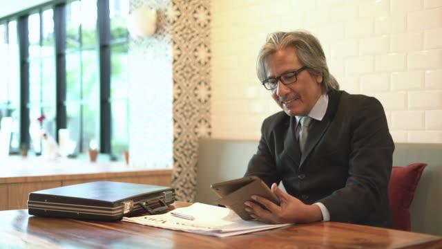 シニア ビジネス カフェで彼のタブレットを使用している人。 - 中年点の映像素材/bロール