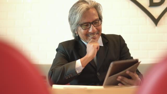 シニア ビジネス カフェで彼のタブレットを使用している人。 - タブレット端末点の映像素材/bロール