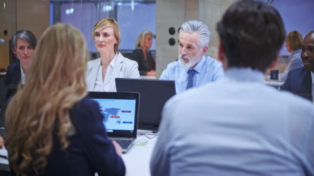 senior business man with grey beard consulting his female colleague during the meeting in the conference room - small group of people stock videos & royalty-free footage