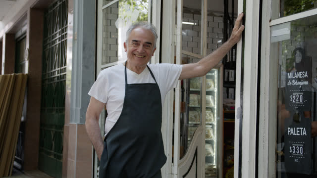 senior business owner of a butcher's shop leaning his hand against the wall smiling at camera - america latina video stock e b–roll
