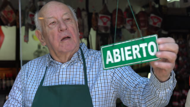 senior business owner of a delicatessen opening for service smiling at camera very happy - argentina america del sud video stock e b–roll