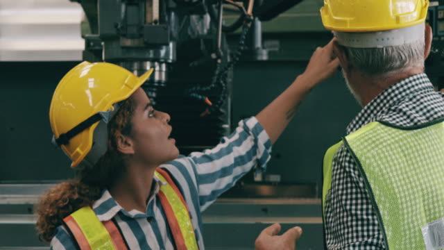 vidéos et rushes de propriétaire principal d'entreprise parlant à l'ouvrier d'usine de femme sur la façon d'actionner la machine. - non us film location