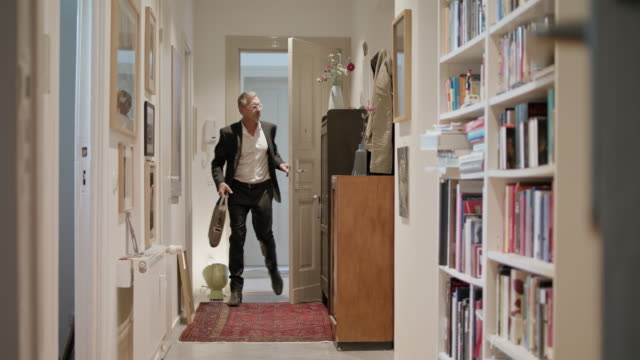 vidéos et rushes de senior business single man in his 60s with short greying hair, grey beard and eyeglasses wearing classic black suit and white shirt coming home from work. - house