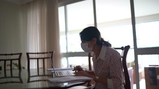 vídeos de stock, filmes e b-roll de mulher de negócios sênior que trabalha em casa usando máscara de proteção - isolado