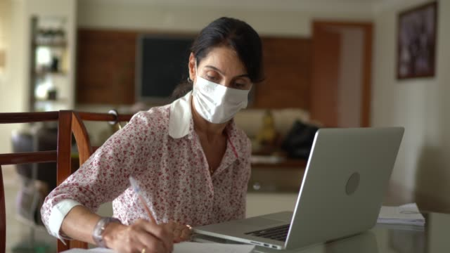 senior business woman working from home wearing protective mask - housework stock videos & royalty-free footage