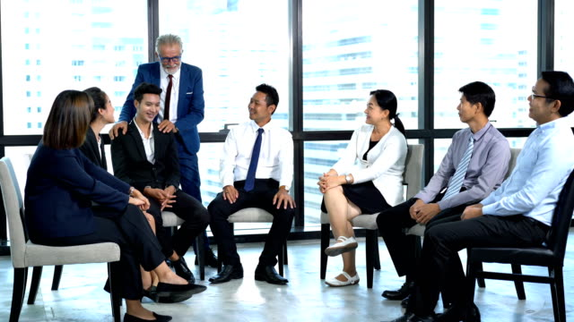 senior businessman brainstorming with business team in the meeting room. leadership give a talk to young business people during business talk at conference event. smiling managing director making great business discussion with young businessmen and busine - business talk stock videos & royalty-free footage